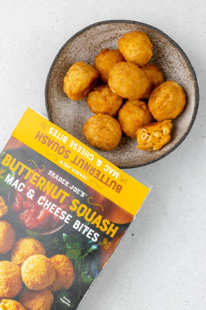 Fully cooked Trader Joe's Butternut Squash Mac and Cheese Bites with one open next to the box.